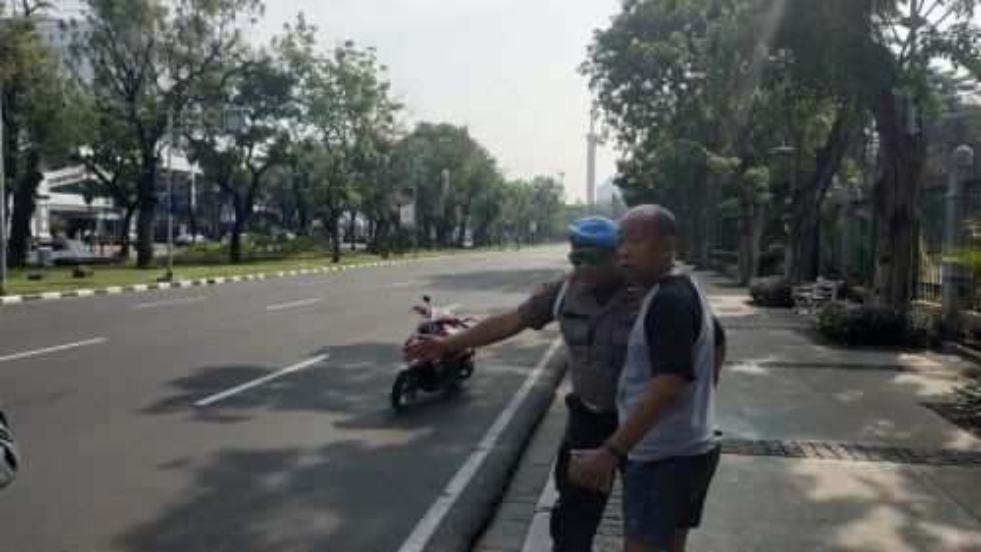 Polisi mengarahkan pejalan kaki menghindari pedestrian Jalan Medan Merdeka Utara, Jakarta Pusat. Medcom.id/Ilham Pratama Putra.