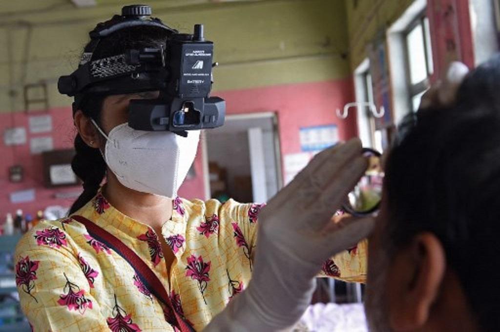 Seorang tenaga kesehatan memeriksa seorang pasien terinfeksi jamur hitam di sebuah rumah sakit di Ahmedabad, India, 23 Mei 2021. (SAM PANTHAKY / AFP)